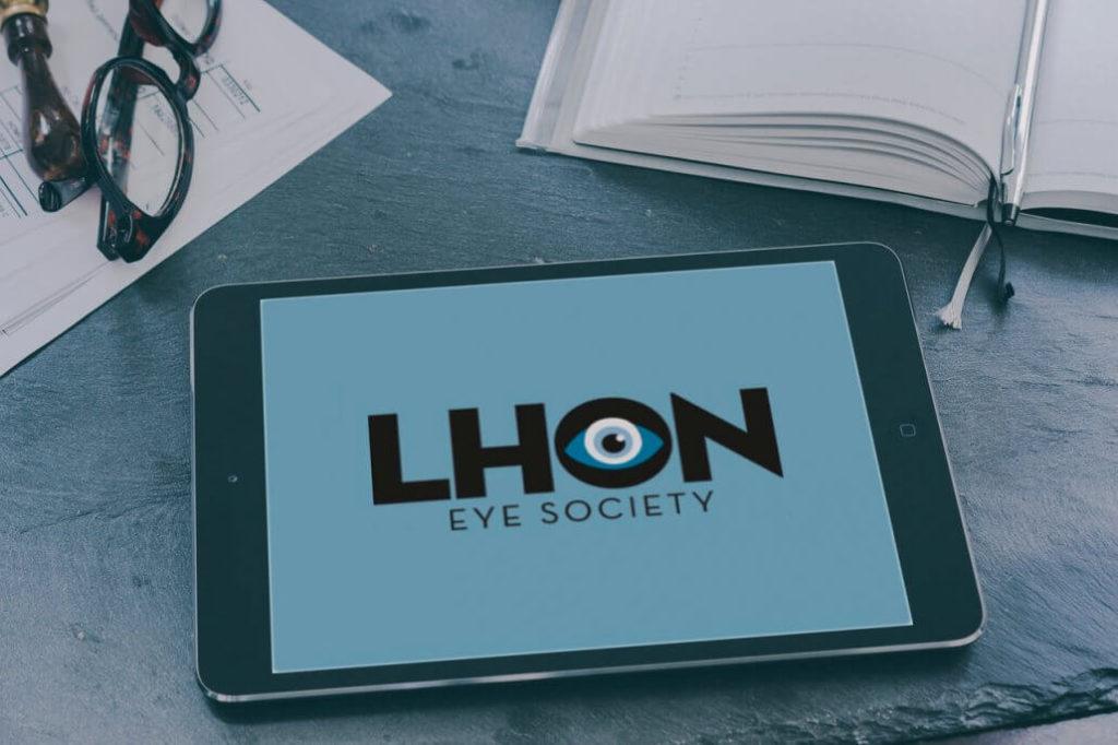 Logga för LHON Eye Society i svart text på blå bakgrund visas på en ipad