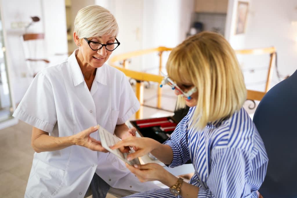 Ögonundersökning, två kvinnor i bild, en sitter med glasögon och en står bredvid och visar text framför